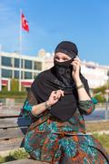 Lady in Black Hijab Holding Telephone and talking - stock photo
