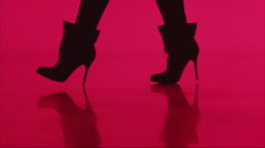 Woman walks in heels, silhouette on red background - Alpha Matte Stock Footage