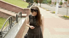 Girl texting on smart phone in the street at sunny weather Stock Footage