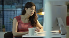 4K Pensive woman working on computer & drinking coffee in city apartment Stock Footage