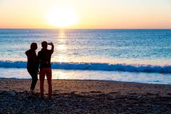 Man and Woman staying on Beach and taking self portrait on telephone Stock Photos