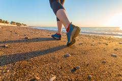 Young Woman jogging on Sand Beach along Sea Surf at Sunrise Shoes Close Up Stock Photos