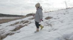 Little girl walking on the field spring landscape Stock Footage