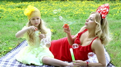 Beautiful woman and girl outdoors blowing bubbles, lying in the grass,smiling. - stock footage