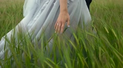 Bride in suit walking ghrough the green field Stock Footage