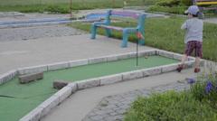 Kid boy child playing mini putt golf Stock Footage
