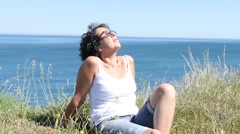 A middle-aged woman with ocean in background Stock Footage