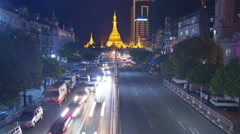 Timelapse of Golden Buddhist Pagoda and Temple at Night With Busy Road Stock Footage