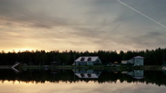 Houses on the edge of the forest. Pond. Sunset. Trace of aircraft in the sky Stock Footage