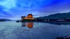 Beautiful sunset at illuminated Eilean Donan Castle over the lake in Scotland Stock Footage