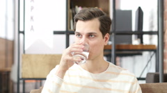 Young man  drinking water sitting on a couch at home and looking at camera Stock Footage