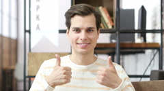 Young man giving thumb up as sign of success Stock Footage