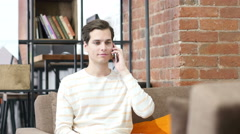 Happy young man sitting at sofa in creative workspace ,answering a phone call Stock Footage