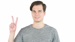 Man showing two fingers or victory sign, isolated, studio Stock Footage