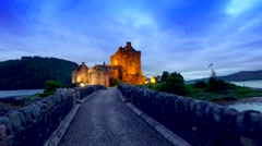 Footpath to the beautiful illuminated Eilean Donan Castle at sunset in Scotland Stock Footage