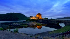 Beautiful dusk at illuminated Eilean Donan Castle over the lake in Scotland Stock Footage