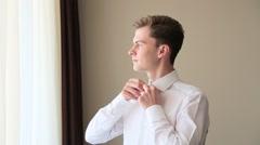 Brunete man buttoning white shirt Stock Footage