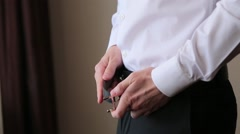 Man in white shirt buckling the belt on his pants Stock Footage