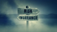 Old Wooden Sign on a Middle of a Cross Road With the Words Risk or Insurance. Stock Footage