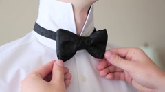 Man corrects black bow-tie on white shirt Stock Footage
