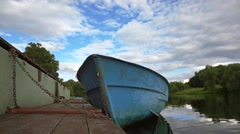 River pier with moored empty blue boat slow motion shot Stock Footage