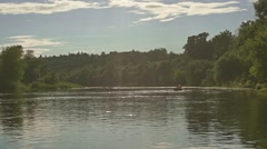Distant people rowing in a boat on the river slow motion shot Stock Footage