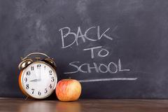 Clock and an apple against a blackboard Stock Photos