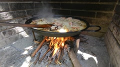 Preparing large dish of paella with firewood Stock Footage