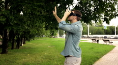 Young handsome man wearing virtual reality headset in city park Stock Footage
