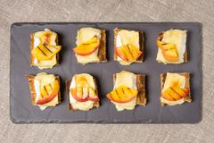 canapes with grilled brie and nectarine - stock photo