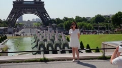 FRANCE, PARIS: Street in front of Eiffel Tower with girl posing for picture Stock Footage
