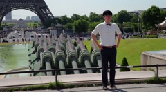 FRANCE, PARIS Street in front of Eiffel Tower with man posing for picture Stock Footage