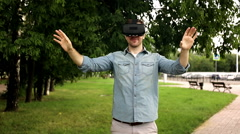 Young handsome man wearing virtual reality goggles in city park Stock Footage