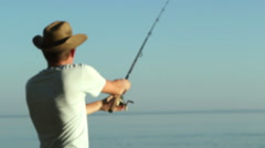 Fisherman on the lake in a cowboy hat. - stock footage