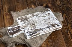 Old cutting board with burlap cloth on wooden table Stock Photos