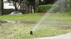 Slow motion wide shot of lawn sprinkler in a neighborhood yard Stock Footage
