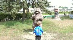 Child comes up to a big bear and shake its paw Stock Footage