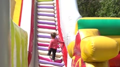 Child climbing stairs of bouncy castle Stock Footage