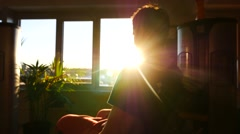Blurred view of a young man working out in a gym in sun rays from the window Stock Footage