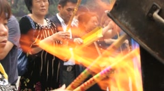 People pray and burn incense in the Yonghe temple in Beijing, China. Stock Footage
