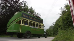 Tourists on open top vintage bus drive through a country lane in Amberley Museum Stock Footage