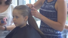 Stylist Makes a Ponytail For Blonde Girl Client Kid in Hairdresser Salon Stock Footage