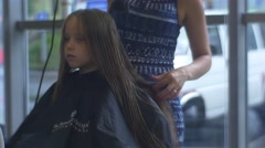 Stylist Combs and Dries Long Hairs of Blonde Kid Hairdresser Salon Female Stock Footage