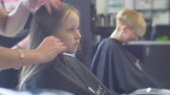 Hairdresser Combs a Hair of the Fair-Haired Girl Stock Footage