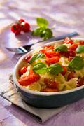 Italian Farfalle pasta with tomatoes and basil Stock Photos