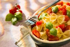 Closeup of Italian Farfalle pasta with tomatoes, basil and fork Stock Photos