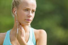 Blonde woman checking her pulse after a long run - stock photo