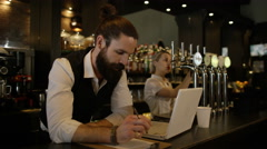 4K Bar owner working on laptop & discussing business plan with female colleague Stock Footage