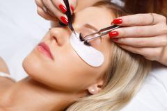 Eyelash Extension Procedure. Woman Eye with Long Eyelashes. Lashes, close up Stock Photos