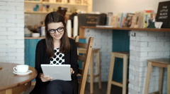 woman sits at a table at a restaurant. carried a tablet with access to Internet - stock footage